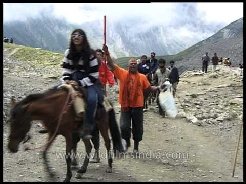 Hindus on ponies walk along a mountain trail to Amarnath Cave