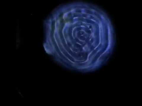 "Walking droplet ""orbiting"" in Faraday standing wave pattern"