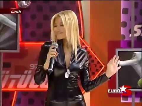 Zeynep Mansur in black PVC or Latex catsuit performing her song