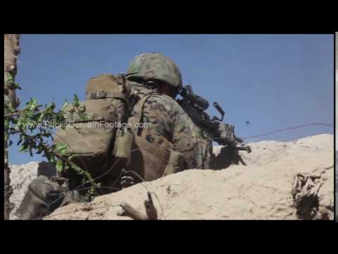 War in Afghanistan - U.S. Marines Firing over wall in fire fight archival footage