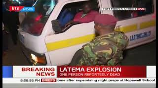 Police push back crowds forming around the scene of the Latema Road explosion