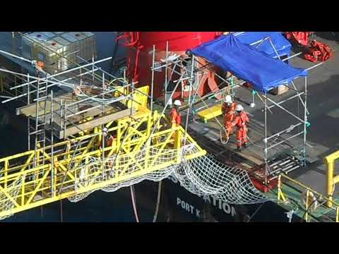 Working crew transfer from oil platform to floating accommodation barge in offshore