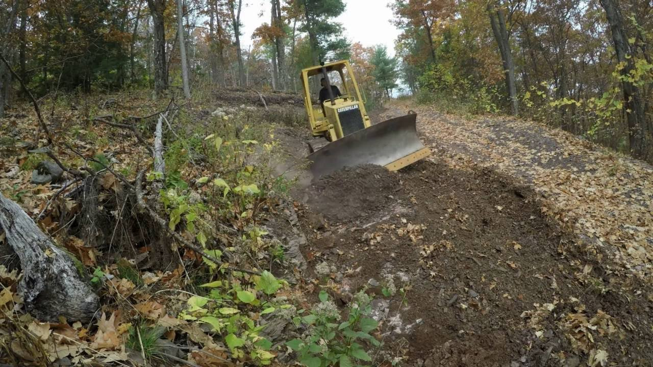Bulldozer grading driveway hill youtube for Steep driveway construction