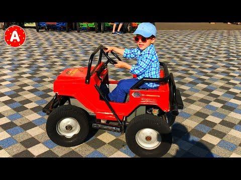 Petit Garçon Adam Conduit Jouet Voiture Electrique pour les Enfants et s'Amuse sur la Plage