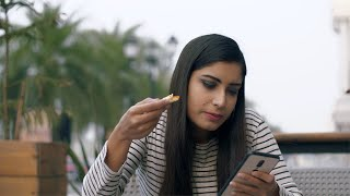 Beautiful Indian girl eating delicious pizza and using her smartphone at the same time