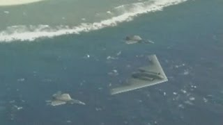 F-22A Raptor Aircraft & B-2 Spirit Stealth Bomber Fly Over Guam