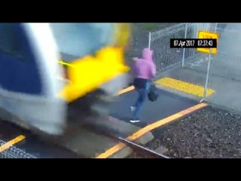 Clueless woman extremely lucky to avoid getting hit by train