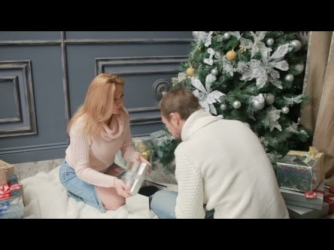 young married couple arranges gifts under the christmas tree stock footage videohive