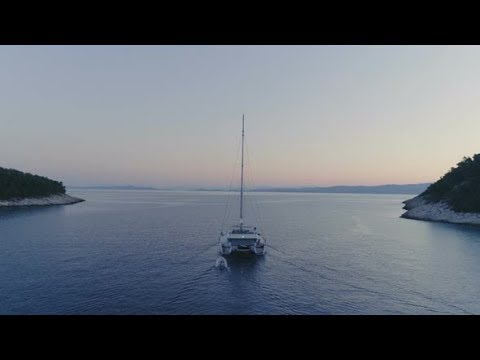 Tranquil Aerial Shot of a Catamaran Yacht Sailing out of the Beautiful Bay. | Stock Footage -