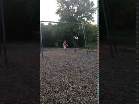 Annika Pushing her doll on the swing