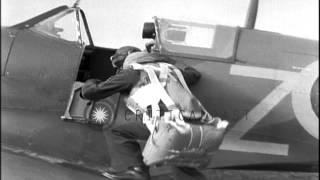A Royal Air Force pilot runs to his Spitfire aircraft, dons his parachute, jumps ...HD Stock Footage