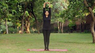A young girl practicing tadasana / mountain yoga pose outside in a park