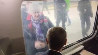 Starsza kobieta pozdrawia Donalda Tuska. Przez szybe i na migi