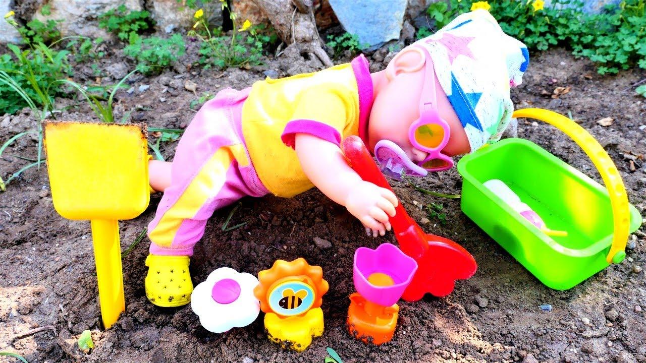 La muñeca bebé va a plantar flores. Vídeos de juguetes para niñas. Juegos con moldes de barro