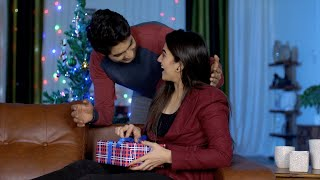 A handsome young man surprises his girlfriend with a colorful gift on Christmas