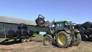 Unloading Round Bales with John Deere 6310.