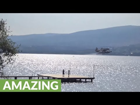 Aircraft uses lake to battle raging forest fires