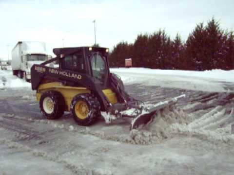 New Holland Skid Steer Loader Plowing Snow
