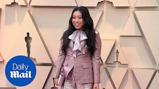 Awkwafina glitters in a pink suit with bow at the 2019 Oscars