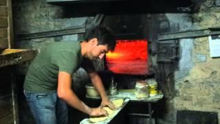Camping Moli Serradell. El enfornant una coca al forn de llenya. Sergi