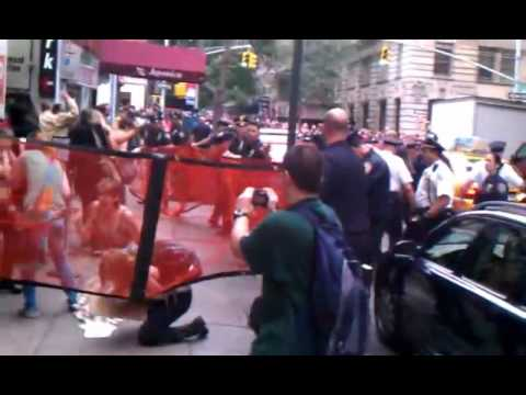 AT OCCUPY WALL STREET PEACEFUL A FEMALE PROTESTORS IS PENNED IN THE STREET AND MACED