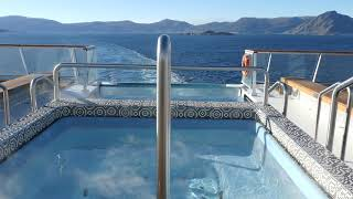 Hot tub and infinity pool looking over ocean wake of Viking Sky cruise ship in Norway