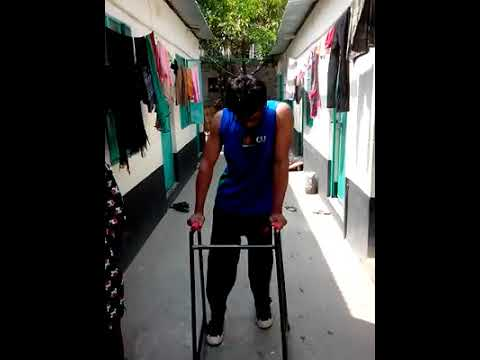 A Paraplegic Man Wearing Caliphers Is Walking In The Courtyard Of His House.