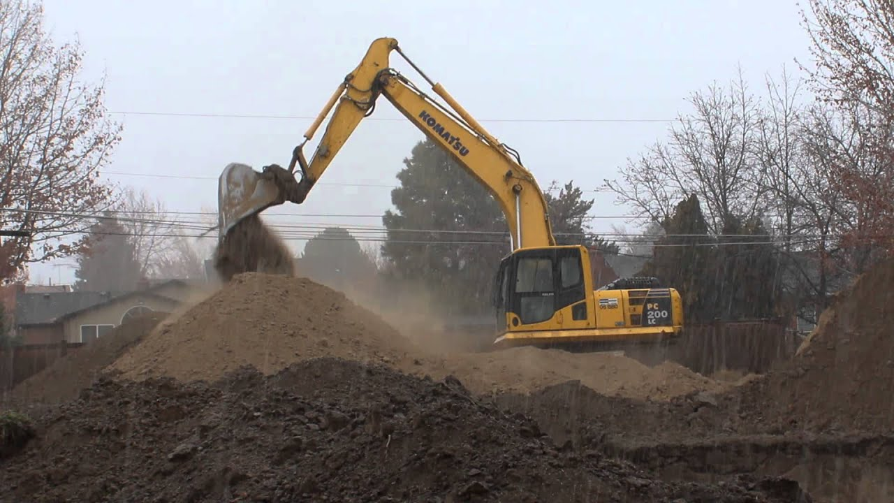 Komatsu pc200lc excavator working in snow and rain digging for Digging foundation for house
