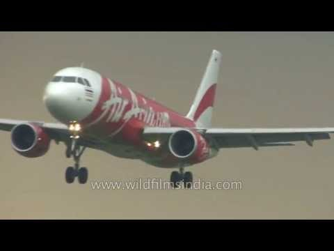 Thai Air and Air Asia planes come in to land at Bangkok airport