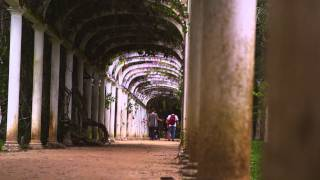 Panning Shot Of Couple Walking Under Famous Arches In Botanical Gardens.