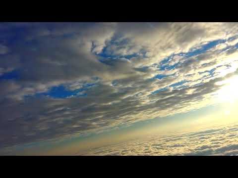 那覇空港テイクオフ。下層雲から中層雲の間を朝日を浴びながら上昇。