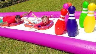Stacy y papá juegan en un jardín con juguetes de agua