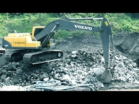 Volvo Excavator Dredge and Grading Rocks on the side of River