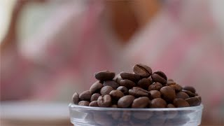 Shot of rotating coffee beans in a bowl while women having coffee in the background