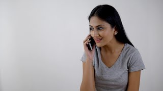 Pretty Indian girl is excited while talking over a phone call against the white background