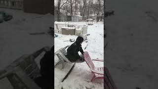 Kid Playing on Chair Outdoors in Snow Faces Fall - 1020660