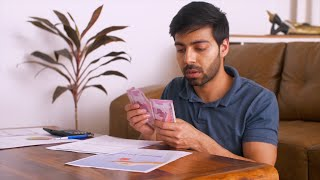 Worried Indian man counting money: Indian currency Rs 2000 notes - Making notes, calculating bills