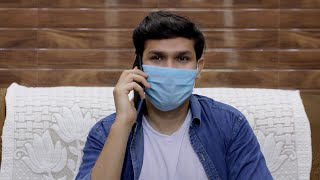Attractive Indian guy talking on his smartphone while wearing a surgical mask