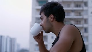 Young Indian boy / man in his house balcony watching the sunset and drinking tea / coffee