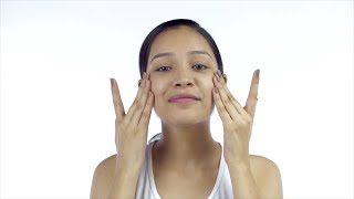 Beautiful girl rubbing moisturizer on her face using her hands - Skincare Concept