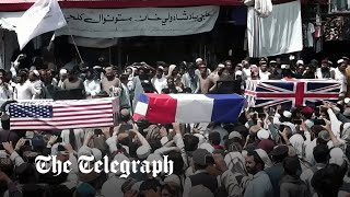 video: Taliban parade coffins draped in UK and US flags as they celebrate 'independence day'