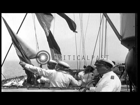 Sailors stand in formation on deck and raise semaphore flags to signal ships unde...HD Stock Footage