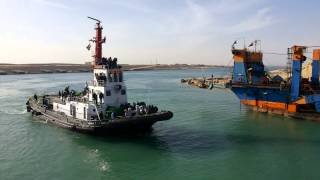 See hotel workers and dredgers and boats in the channel of communication