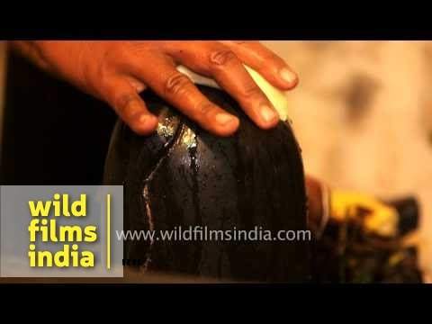 Hindu priest places banana atop Shiva