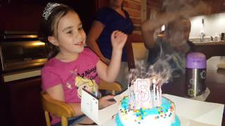 Alexis' blows out the relighting trick candles on her 5th birthday cake