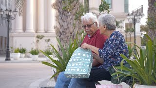 Retired old couple enjoying shopping day together in city streets - lifestyle concept