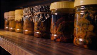 Pan shot of ready Indian pickles / achar kept in bottles for sale