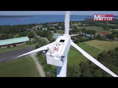 Drone sorprende a un hombre descansando sobre una turbina eólica