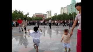 新疆ウイグル自治区アクス市の広場で踊る人々