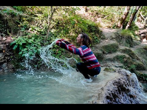 Ingrid in river with old Nike, socks, jeans and sweater